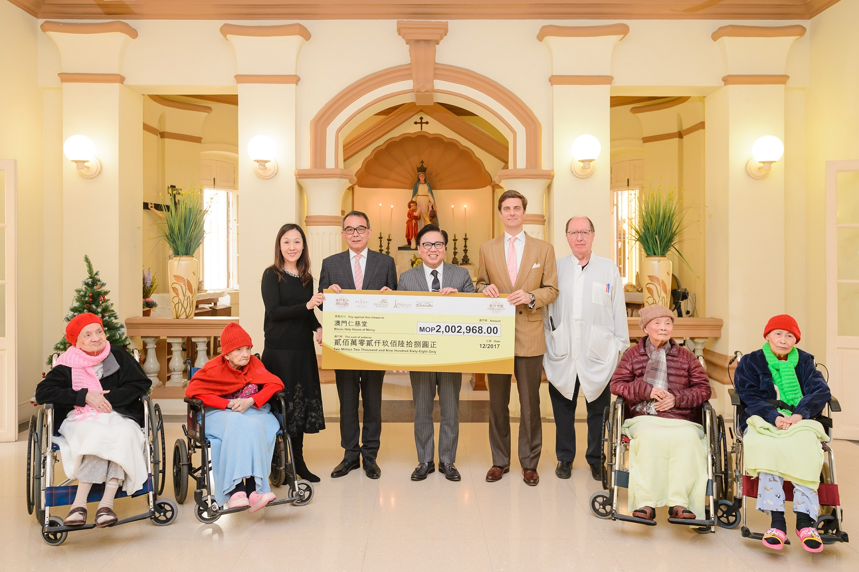 Sands China President Dr. Wilfred Wong (standing centre) and Vice President of Corporate Communications and Community Affairs Winnie Wong (standing left) present a MOP 2 million cheque to Macau Holy House of Mercy